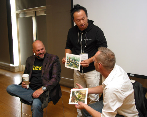 Daniel Chang (center), founder and CEO of VintageMagic.com, holds the original artwork for the Magic: The Gathering card People of the Woods during a presentation with original Magic artists Mark Poole (left) and Drew Tucker at IX8. Tucker, holding the original artwork for Night Soil, painted both pieces.